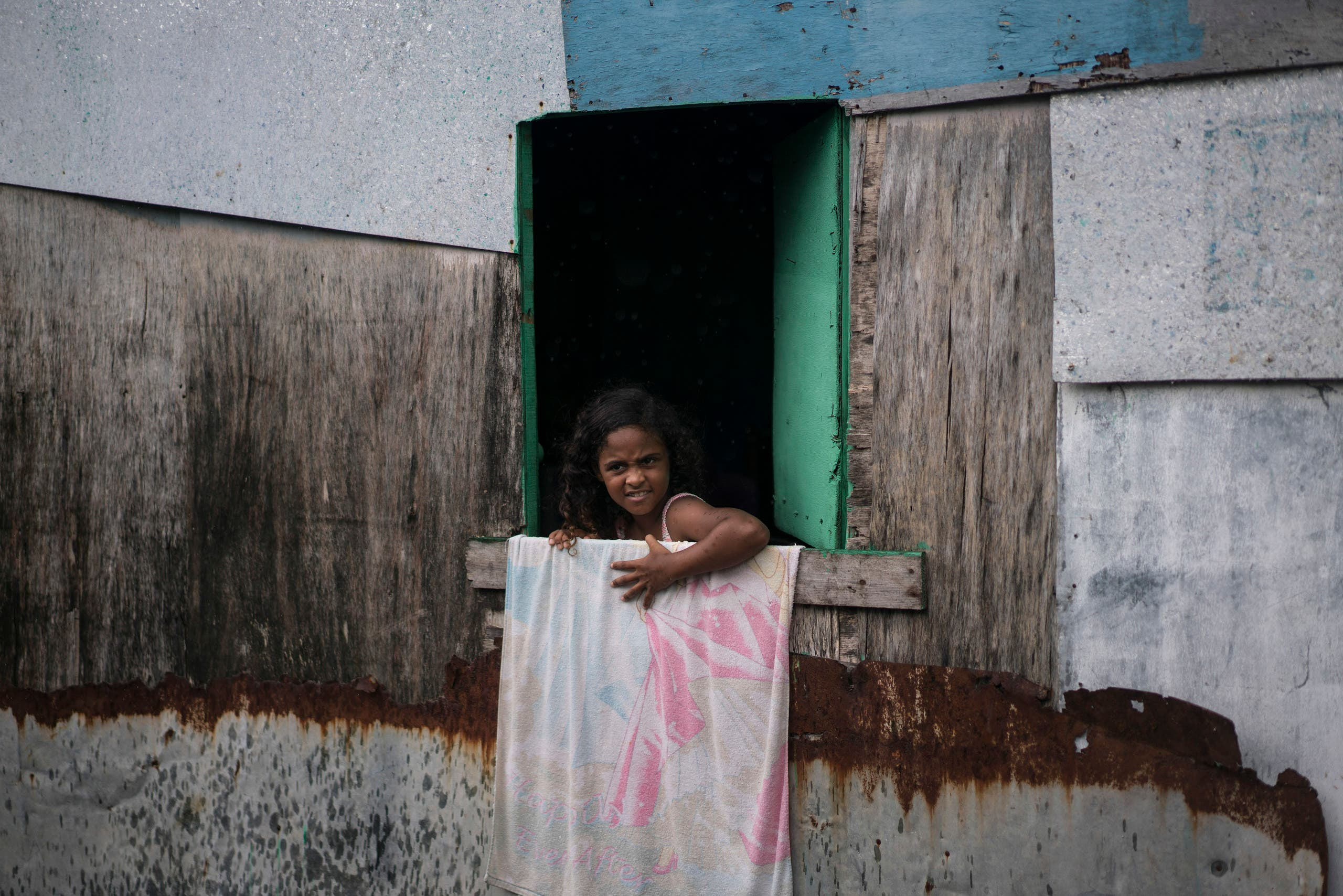 In this Jan. 29, 2016 photo, a girl looks out from her stilt house, built over a polluted body of water at a slum at the epicenter of Brazil's tandem Zika and microcephaly outbreaks, in Recife.