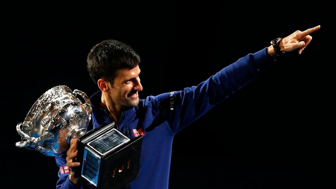 Novak Djokovic of Serbia waves as he walks around Rod Laver Arena after defeating Andy Murray of Britain in the men's singles final at the Australian Open tennis championships in Melbourne, Australia, Sunday, Jan. 31, 2016.