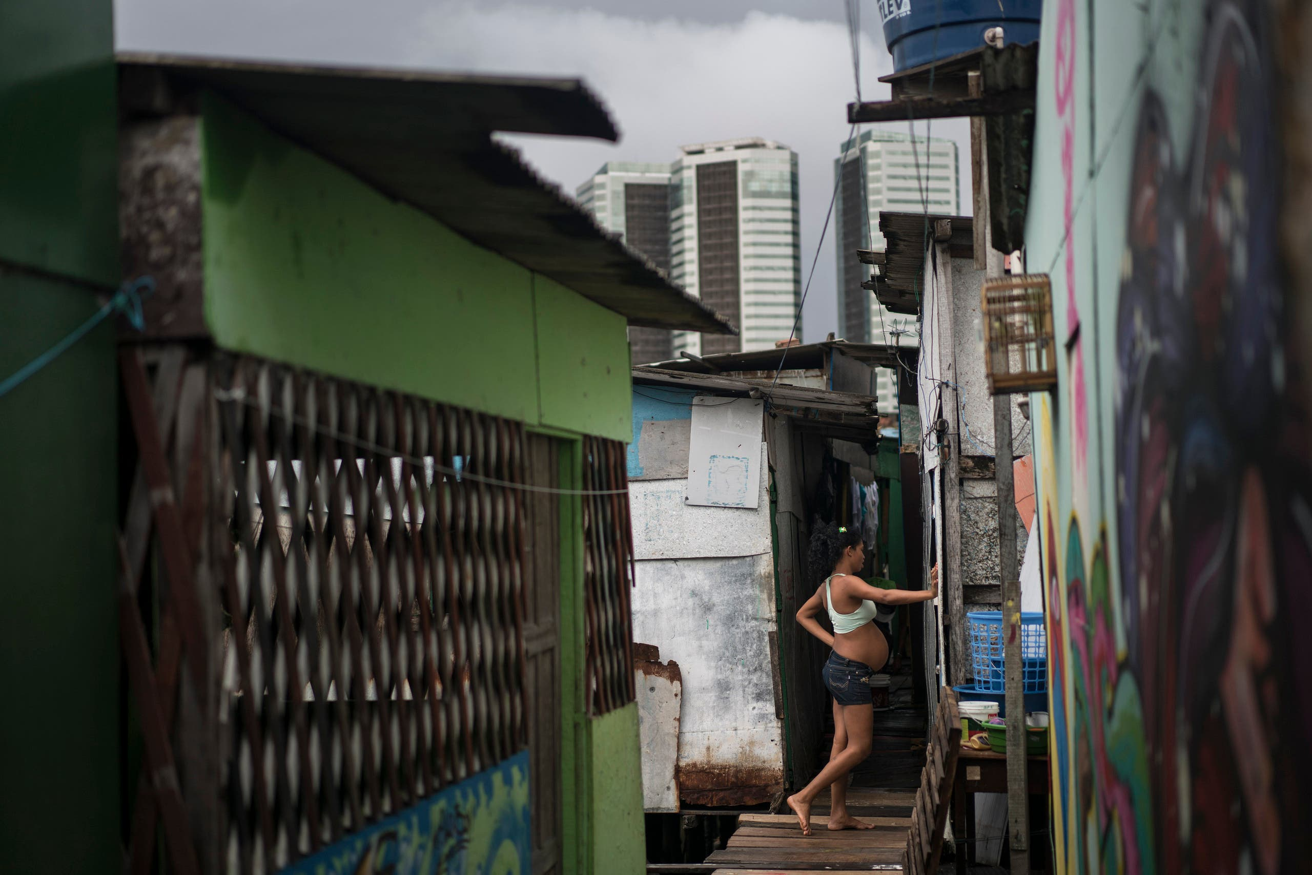 In this Jan. 29, 2016 photo, Tainara Lourenco, who is five months pregnant, stands outside her stilt home, built over a polluted body of water at a slum in Recife, Brazil.