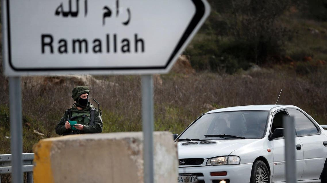 An Israeli soldier checks the documents of the passengers of a Palestinian car on a road leading to the West Bank village of Ein Sinya, northern Ramallah. (AFP)