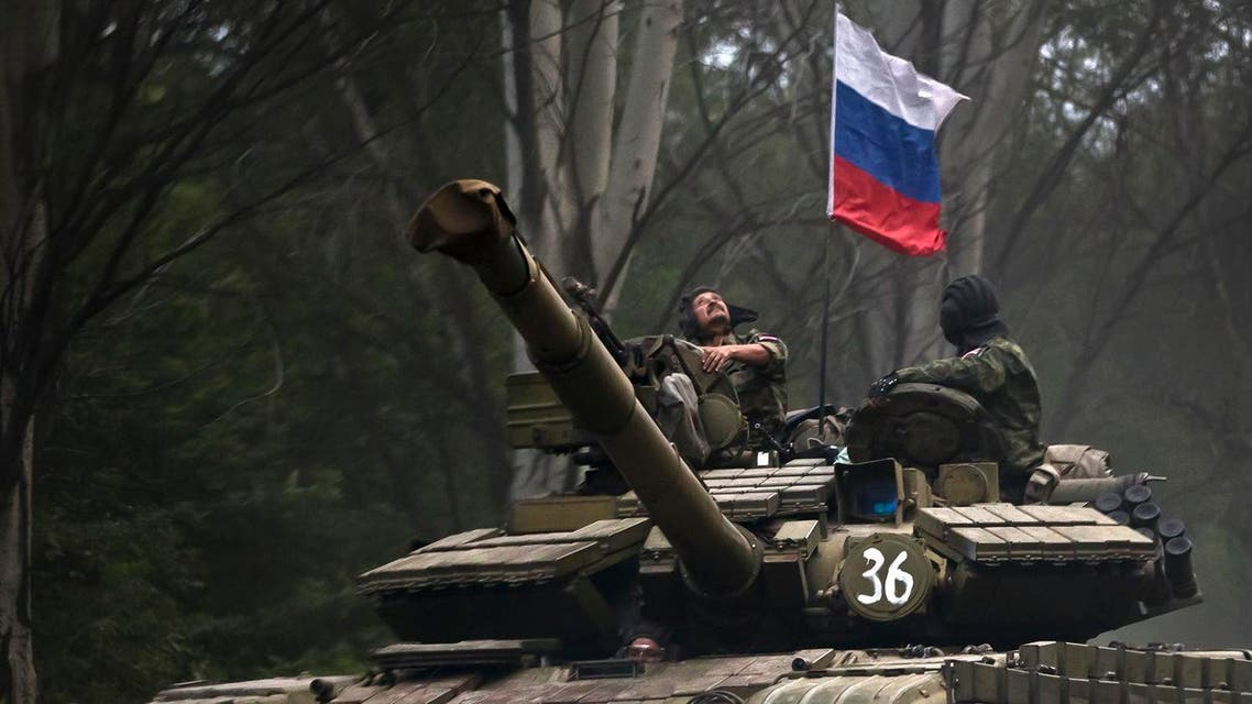 A pro-Russian rebel looks up while riding on a tank flying Russia's flag, on a road east of Donetsk, eastern Ukraine. (File photo: AP)