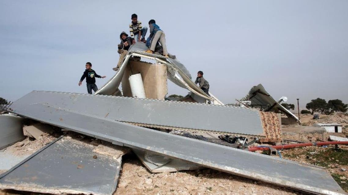 Palestinian Bedouins play around the remains of makeshift homes that were demolished by the Israeli army in the West Bank city of al-Azariya, on January 21, 2016 (AFP)