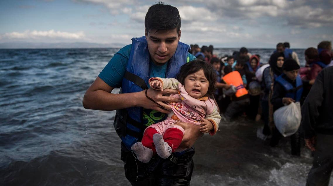 A man holding a baby disembarks from a dinghy after arriving from a Turkish coast to the northeastern Greek island of Lesbos. (File photo: AP)