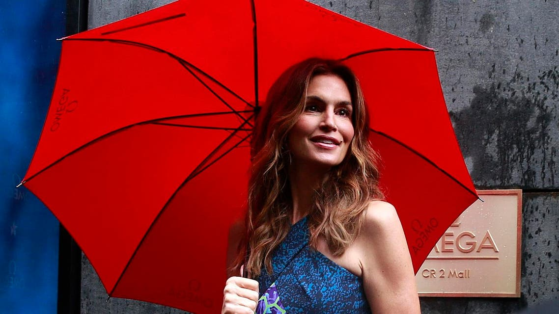Former supermodel Cindy Crawford holds an umbrella as she poses for photographs at a promotional event for Omega's new Constellation Pluma Collection in Mumbai, India. (AP)