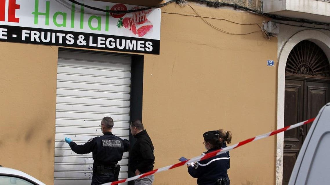 Police officers look for evidence at a Muslim butcher's shop that was sprayed with bullets overnight on February 3, 2016 in Propriano, on the French Mediterranean island of Corsica (AFP)