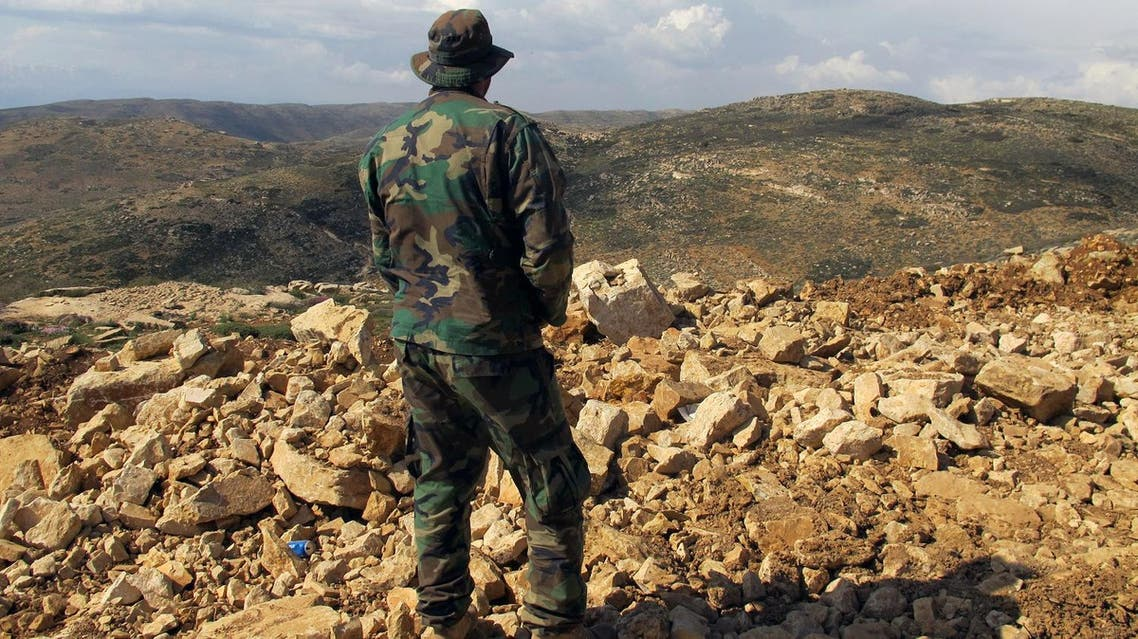 In this Saturday, May 9, 2015 photo, a Hezbollah fighter looks toward Syria while standing in the fields of the Lebanese border village of Brital, Lebanon. (AP)