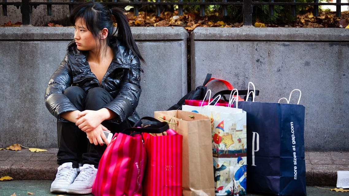 A consumer rests herself and her bags in Herald Square during the busiest shopping day of the year. (File photo: AP)