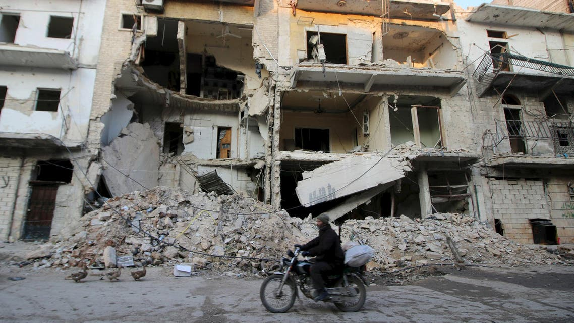 A man rides a motorcycle past damaged buildings in al-Myassar neighborhood of Aleppo, Syria January 31, 2016. Picture taken January 31, 2016. REUTERS/Abdalrhman Ismail
