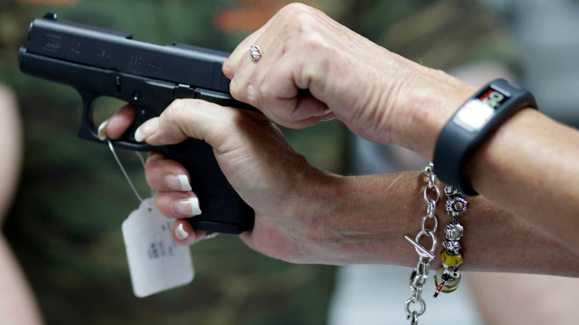 Sally Abrahamsen, of Pompano Beach, Fla., right, holds a Glock 42 pistol while shopping for a gun at the National Armory gun store and gun range. (AP)
