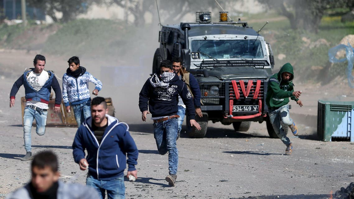 Palestinians run for cover during clashes with Israeli troops in the West Bank village of Qabatya near Jenin, February 4, 2016. REUTERS