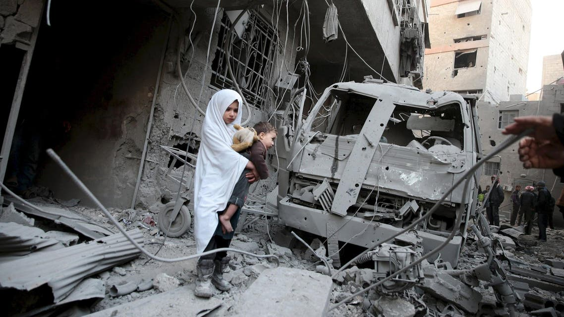 A girl carrying a baby inspects damage at a site hit by what activists said were airstrikes carried out by the Russian air force in the town of Douma, eastern Ghouta in Damascus, Syria in this January 10, 2016 file photo. To match MIDEAST-CRISIS/SYRIA REUTERS/Bassam Khabieh/Files