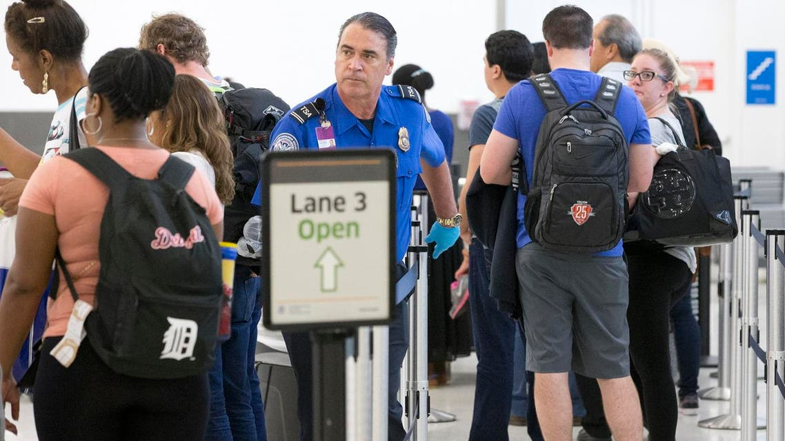 A Transportation Security Administration agent, center, helps passengers navigate through the lines as they pass through security at the Fort Lauderdale-Hollywood International Airport. (File photo: AP)