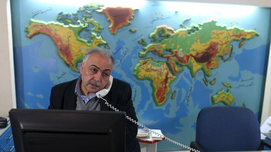 Palestinian travel agent Nabil Shurafa speaks on a phone at his office in Gaza City. (Reuters)