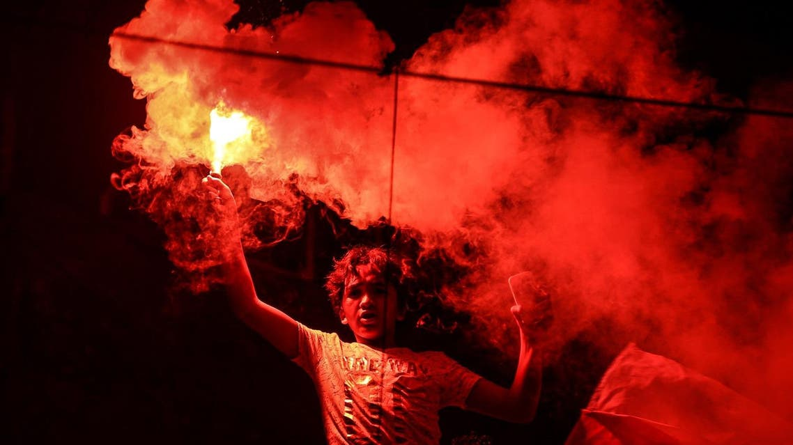 In this July 26, 2015 photo, a member of Zamalek's football club's Ultras White Knights group (UWK), the club's hardcore fan base, lights flares during a friend's bachelor party in Cairo. (AP)