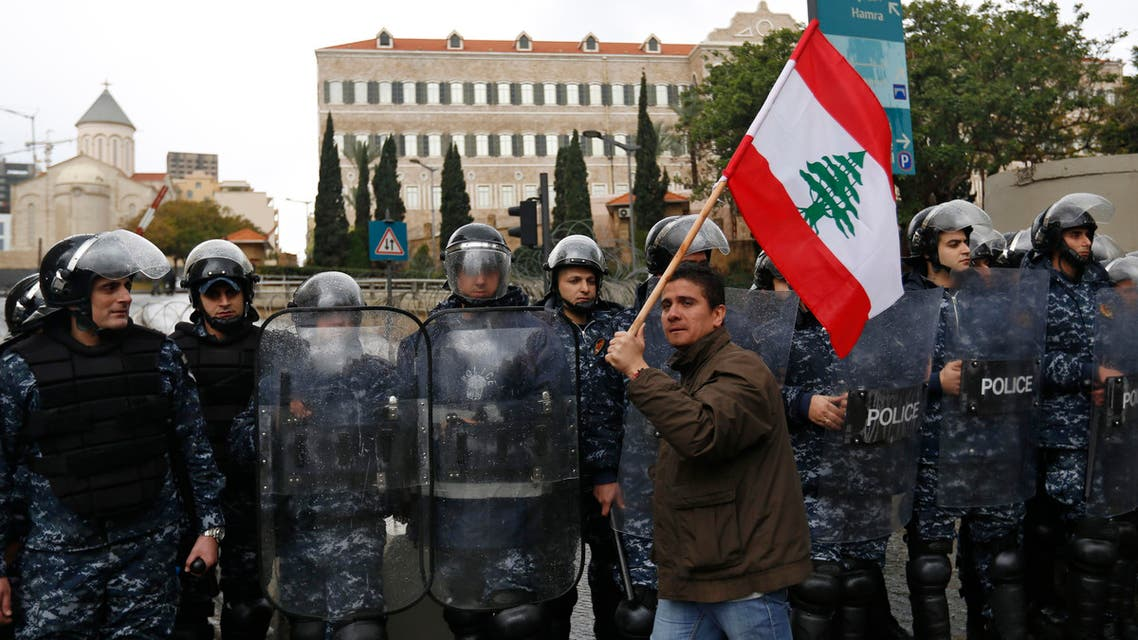 A Lebanese protester holds up a Lebanese national flag in front Lebanese security forces as they stand guard during a protest against the on-going trash crisis and government corruption, in downtown Beirut, Lebanon (AP)