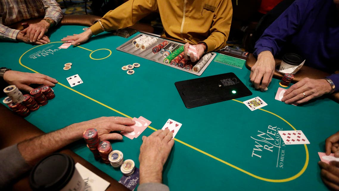 In this Wednesday, Feb. 3, 2016 photo a card dealer deals a game of poker to patrons at Twin River Casino, in Lincoln, R.I. Casinos far from Las Vegas are experimenting with different ways to draw millennials. (AP)