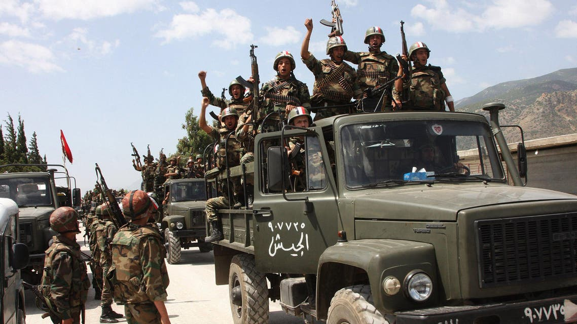 In this June 10, 2011, file photo, taken during a government-organised visit for media, Syrian army soldiers standing on their military trucks shout slogans in support of Syrian President Bashar Assad. AP