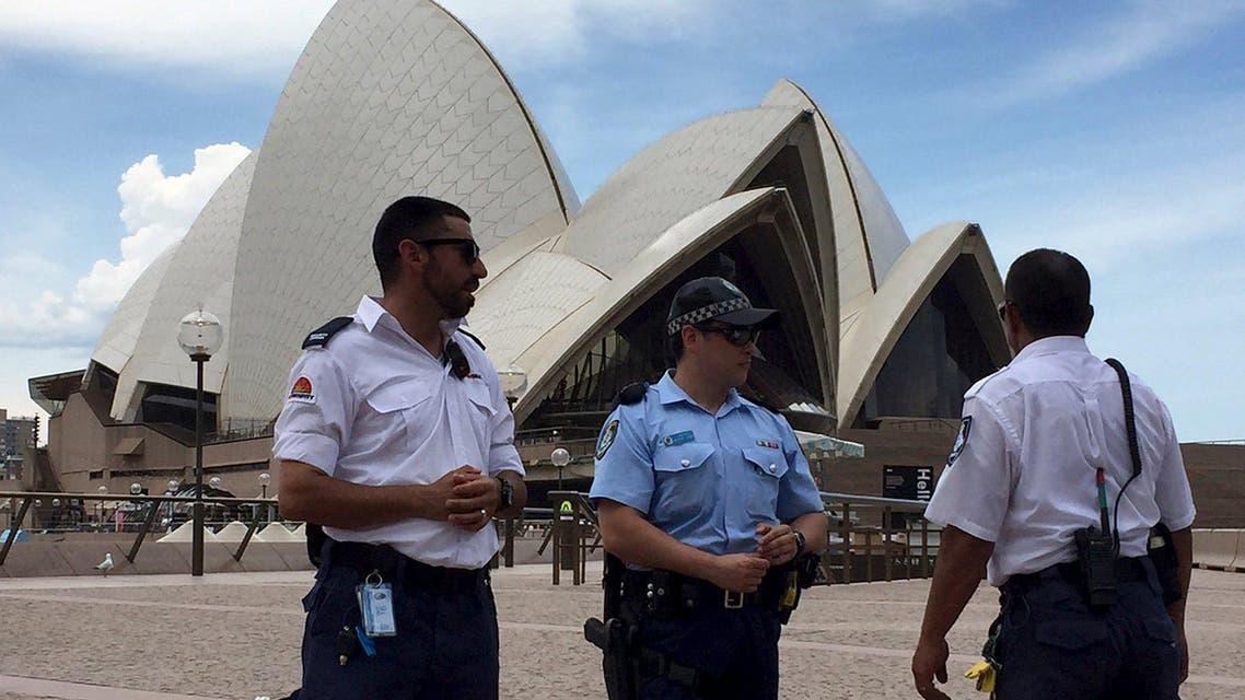 Police and security staff stand in front of the Sydney Opera House after it was evacuated due to a police operation January 14, 2016.