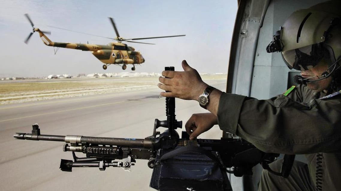 An Afghan soldier adjusts bullets in his gun on a military helicopter during a flight transporting journalists from Kabul to Bagram to attend the hand over ceremony of U.S.- run prison to Afghan government in Bagram north of Kabul, Afghanistan, Monday, Sept. 10, 2012. U.S. officials handed over formal control of Afghanistan's only large-scale U.S.-run prison to Kabul on Monday, even as disagreements between the two countries over the thousands of Taliban and terror suspects held there marred the transfer. (AP Photo/Musadeq Sadeq)