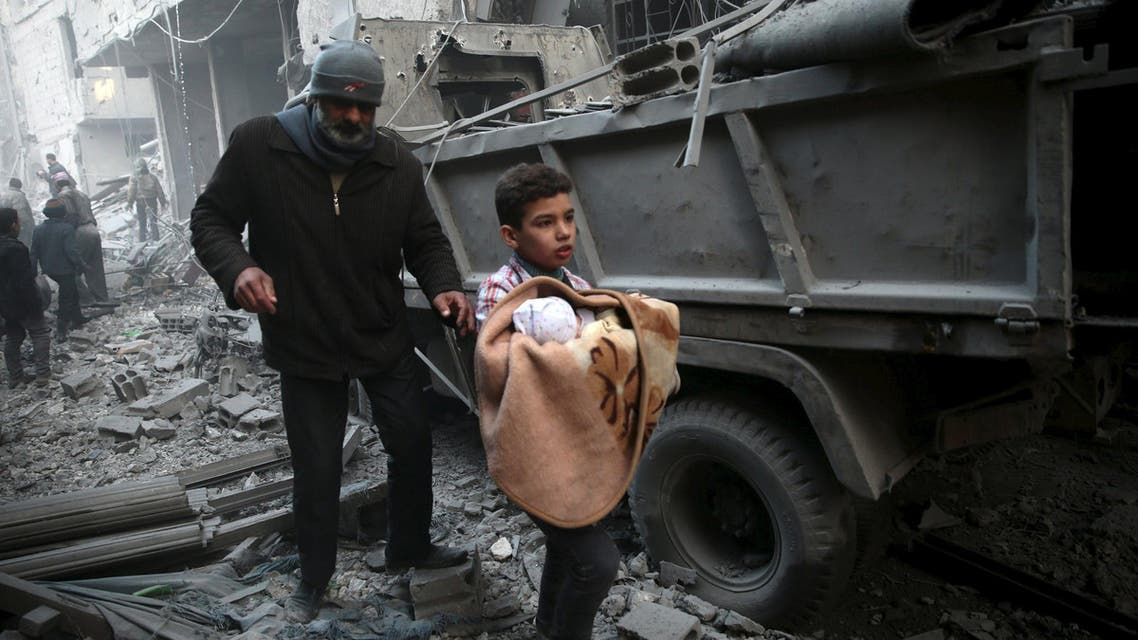 A boy carries a baby in a site hit by what activists said were airstrikes carried out by the Russian air force in the town of Douma, eastern Ghouta in Damascus, Syria January 10, 2016. REUTERS/Bassam Khabieh