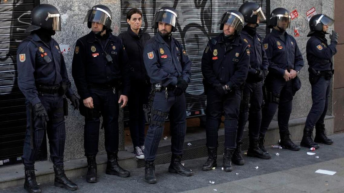 Police riots stand guard in front of a restaurant as the owner waits for the protestors to go away during a general strike in Madrid, Spain, Wednesday, Nov. 14, 2012. Spain's main trade unions stage a general strike, coinciding with similar work stoppages in Portugal and Greece, to protest government-imposed austerity measures and labor reforms. The strike is the second in Spain this year. (AP Photo/Andres Kudacki)  Use Information This content is intended for editor