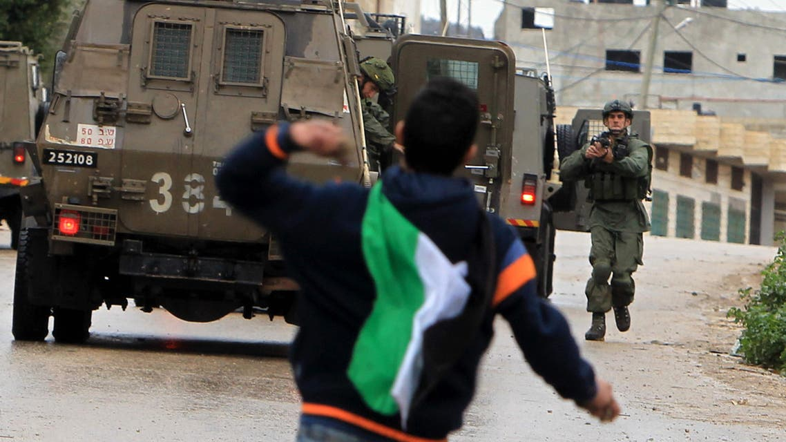 A Palestinian youth throws stones towards Israeli military vehicles in the village of Qabatiya, near the West Bank town of Jenin, during clashes on February 6, 2016.