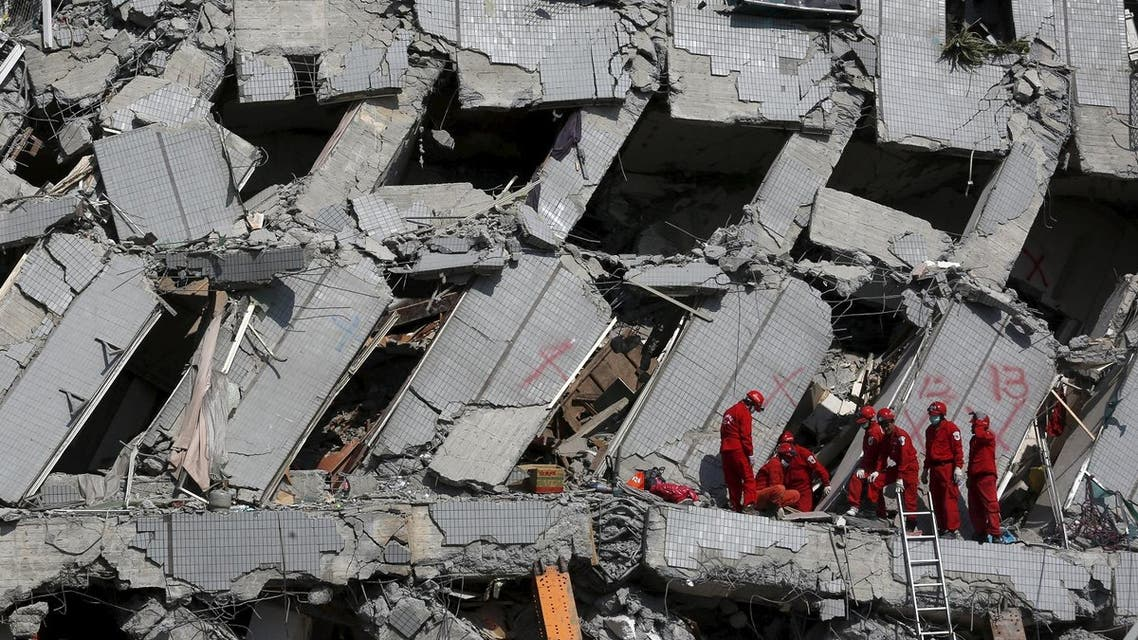 Rescue personnel work at the site where a 17-storey apartment building collapsed after an earthquake hit Tainan, southern Taiwan February 7, 2016. REUTERS