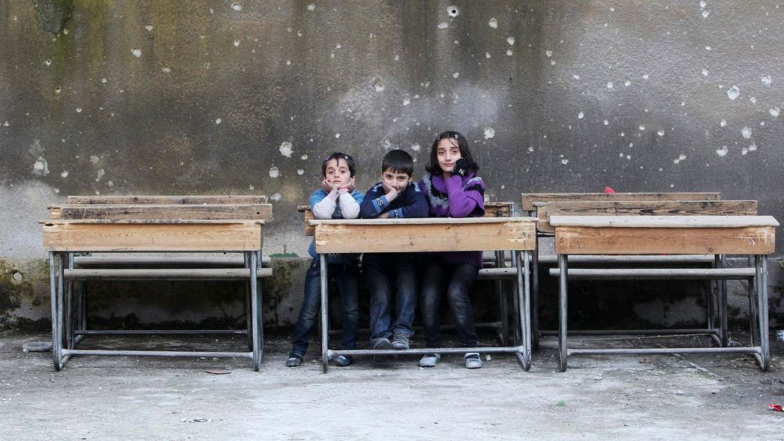 Children sit on school benches at Al-Tawheed school in Aleppo January 1, 2013. (Reuters)