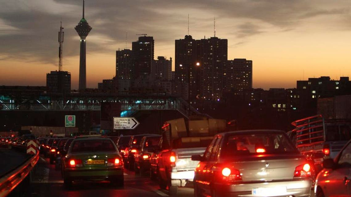 In this Saturday, Nov. 27, 2010 file photo, Milad telecommunications tower and residential towers are seen, as cars drive in an evening traffic jam in Tehran, Iran. The nuclear deal struck by Iran and world powers will provide some relief from sanctions for Iran's automakers. The sanctions relief, due to start in early January, 2014, allows French carmakers PSA Peugeot Citroen and Renault to resume shipping auto parts to Iran for assembly by Iran's biggest carmakers Iran Khodro and SAIPA. (AP Photo/Vahid Salemi, File)