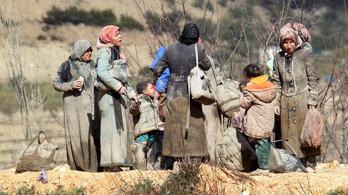Internally displaced people, covered with mud, wait as they are stuck in the town of Khirbet Al-Joz, in Latakia countryside, waiting to get permission to cross into Turkey near the Syrian-Turkish border, Syria, February 7, 2016. REUTERS