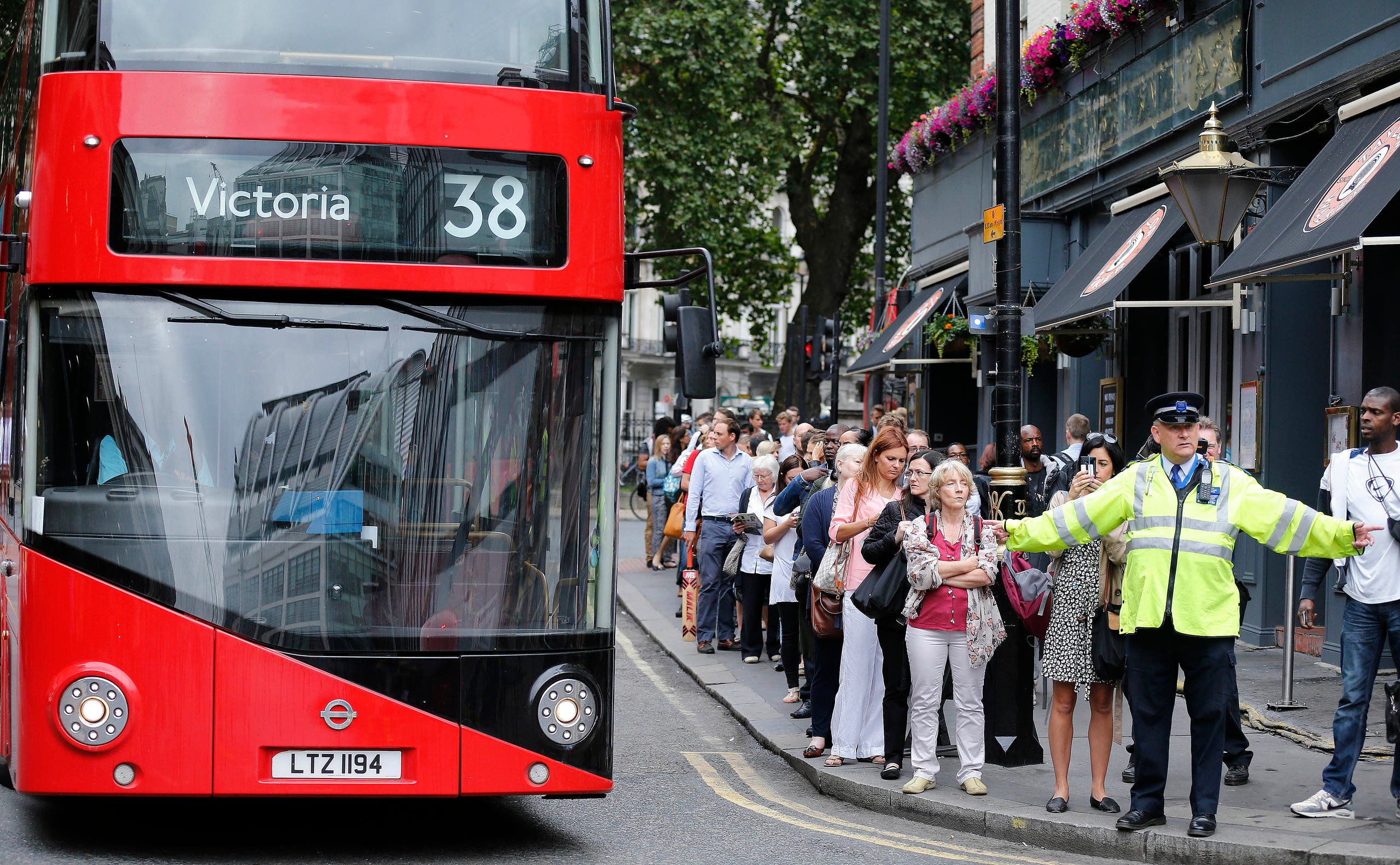 A police officer controls people queuing up for bus transport at Victoria Station in London, Thursday, Aug. 6, 2015. AP