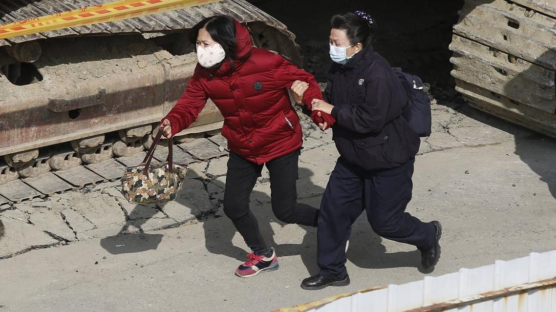 A relative of a missing victim rushes to take a look at survivors saved by rescue workers, after an earthquake in Tainan. (Reuters)