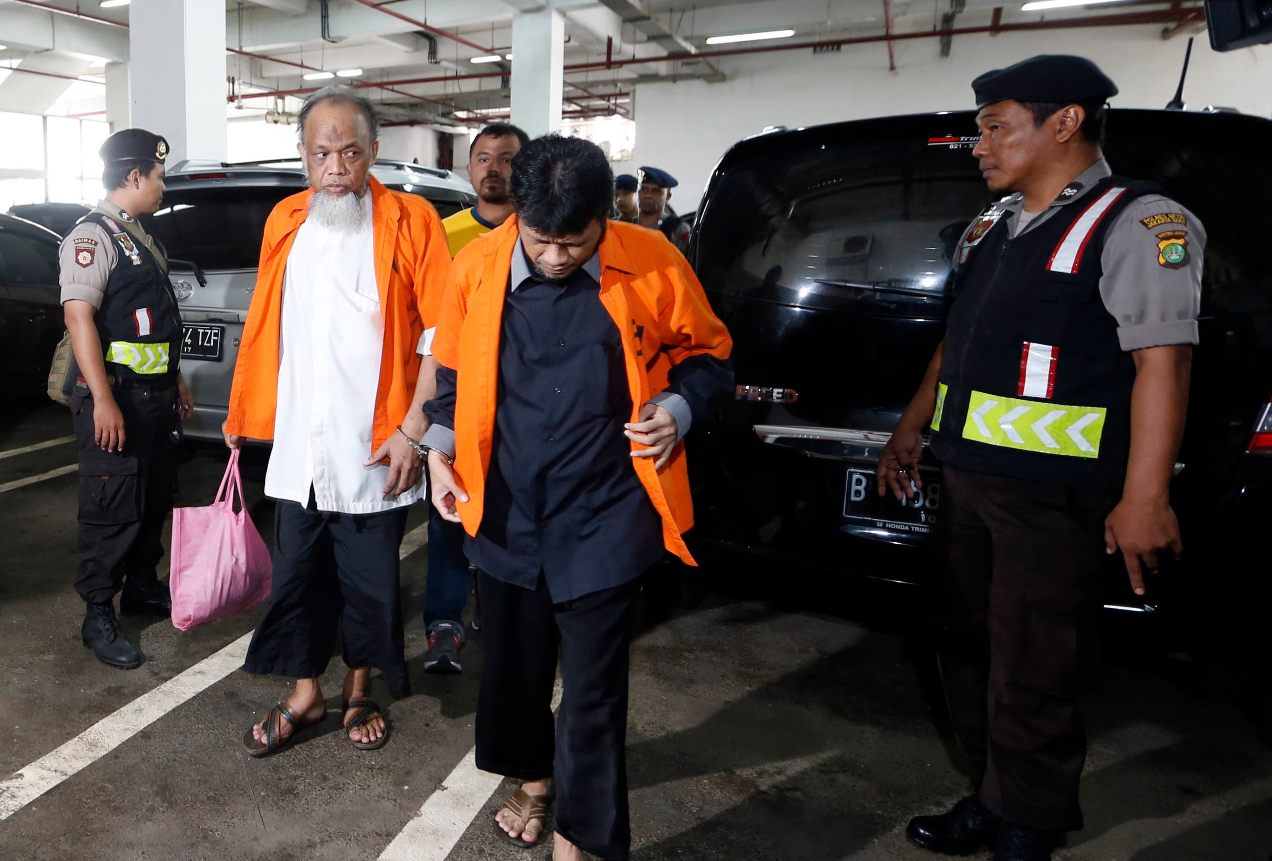 Indonesian policemen stand guard as Muhammad Fachry (2nd R), also known as Tuah Febriansyah and Muhammad Basri (2nd L), who are accused of supporting Islamic State, arrive for their trial at the West Jakarta court in Jakarta, February 9, 2016.