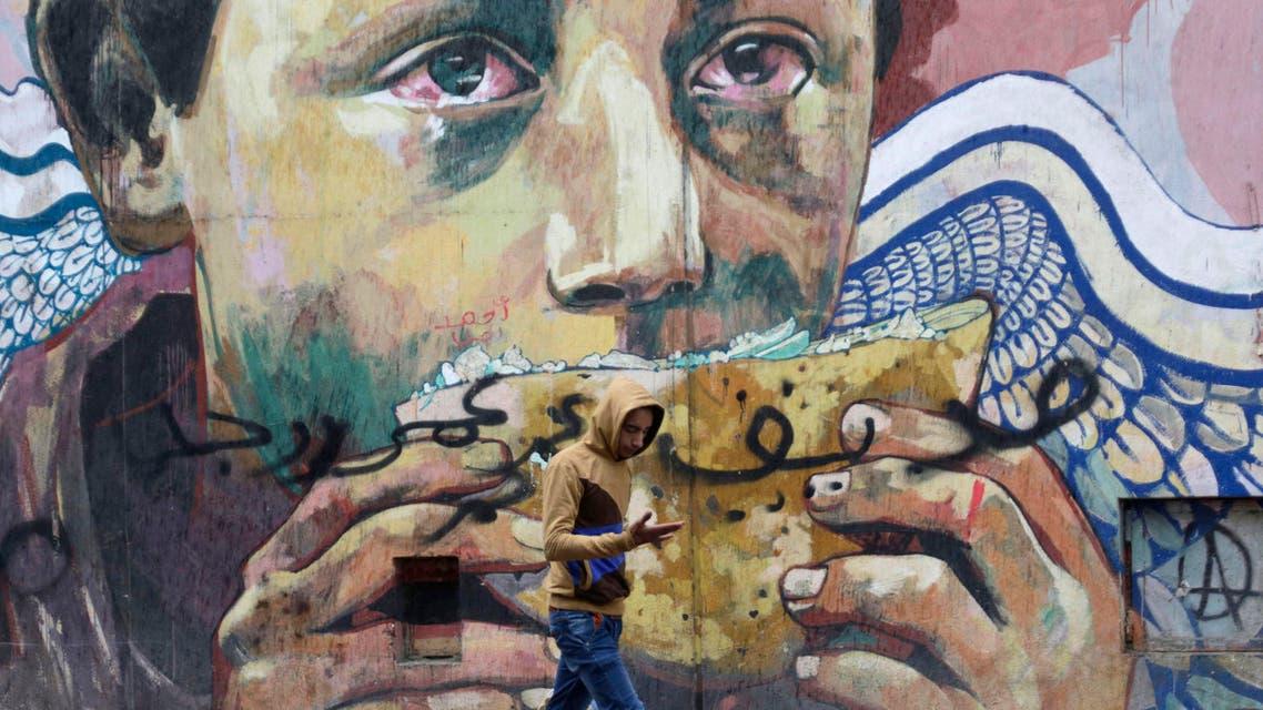 An Egyptian walks past an old mural Mohammed Mahmoud street near Tahrir Square, related to the 2011 uprising that toppled longtime ruler Hosni Mubarak, Cairo, Egypt, Monday, Jan. 25, 2016. (AP)