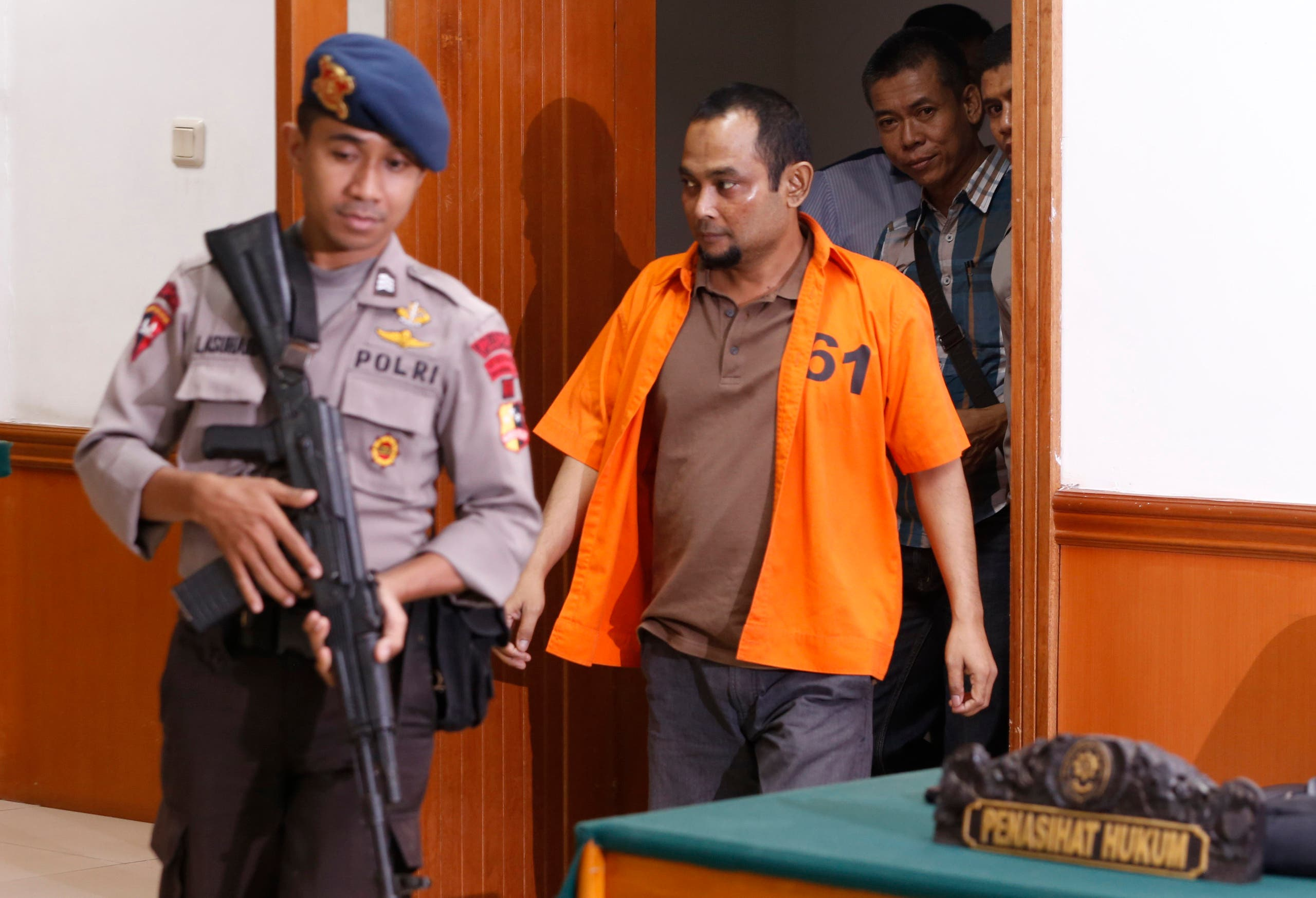 Aprimul Henry (C), also known as Mulbin Arifin, who is accused of supporting Islamic State, is escorted by a policeman as he arrives for his trial at West Jakarta court in Jakarta, February 9, 2016.