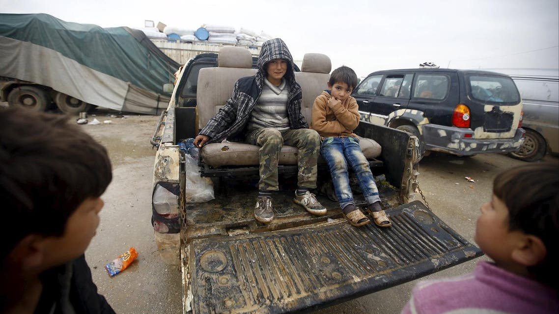 Internally displaced Syrian boys sit in the back of a truck in front of a refugee camp near the Bab al-Salam crossing. (Reuters)