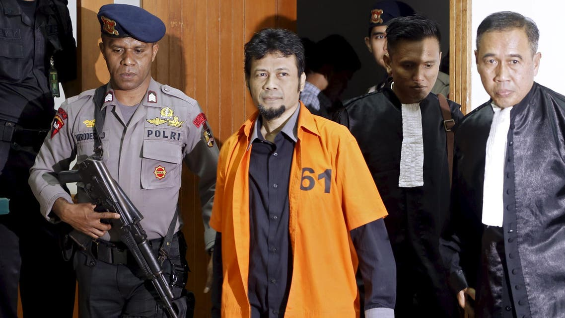 Muhammad Fachry (2nd L), also known as Tuah Febriansyah, who is accused of supporting Islamic State, is escorted by a policeman as he arrives for his trial at West Jakarta court in Jakarta, February 9, 2016. reuters