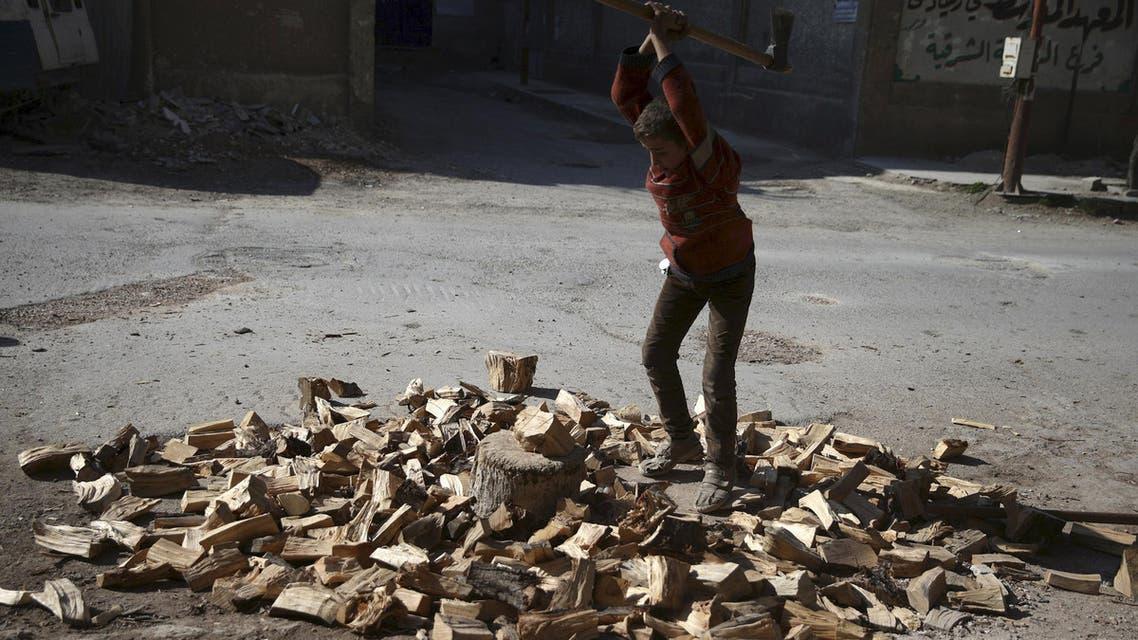 A boy cuts firewood along a street in the Douma neighbourhood of Damascus, Syria February 9, 2016. (Reuters)