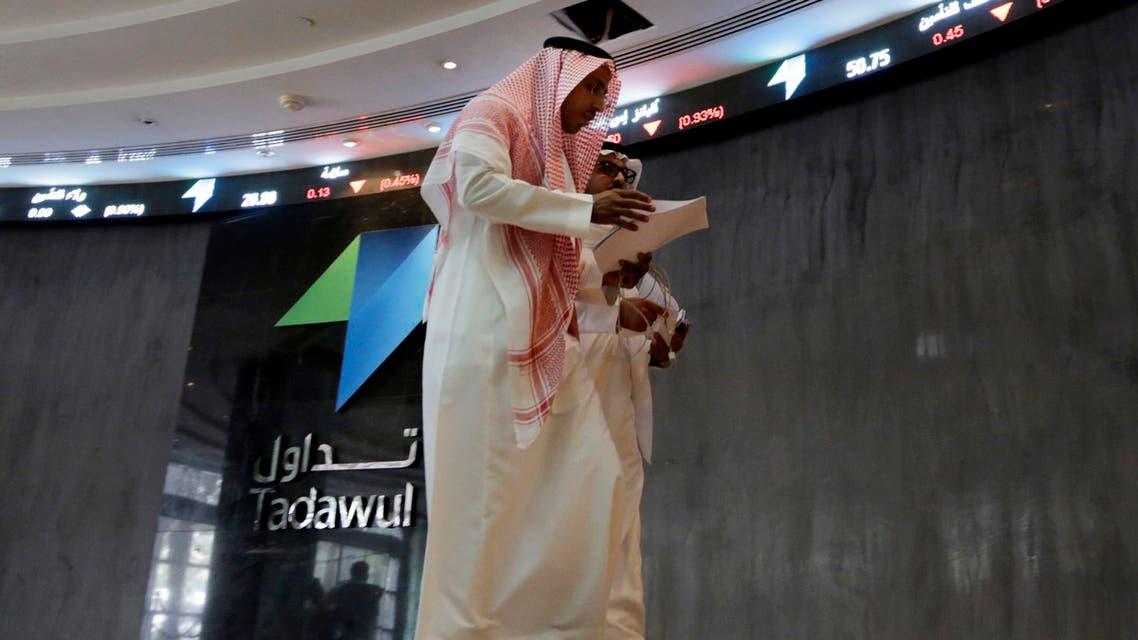 Saudi men walk at the Tadawul Saudi Stock Exchange, in Riyadh, Saudi Arabia, Monday, June 15, 2015. (AP)