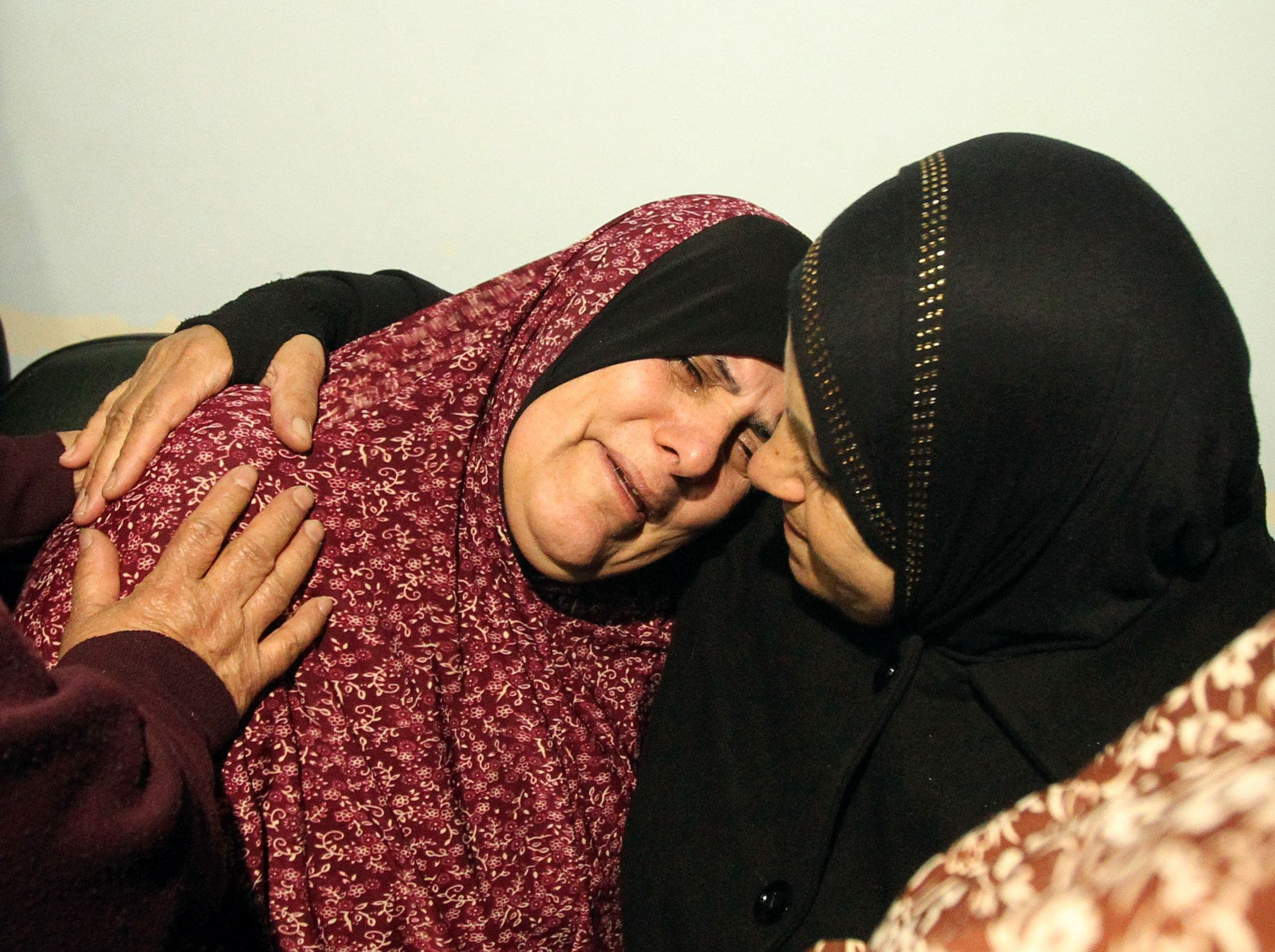 The mother (L) of Palestinian youth Omar Maddi, 16, is comforted by a relative as she mourns the death of her son in the al-Mizan hospital in the West Bank city of Hebron on February 10, 2016 after he was killed during clashes with Israeli security forces in the area of the Al-Arroub refugee camp. afp