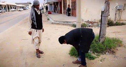 صورة تناقلتها مواقع ليبية لعنصر من داعش يجبر شابا من سرت على رفع سرواله