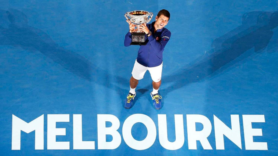 Serbia's Djokovic celebrates with the men's singles trophy after winning his final match against Britain's Murray at the Australian Open tennis tournament at Melbourne Park. (Reuters)