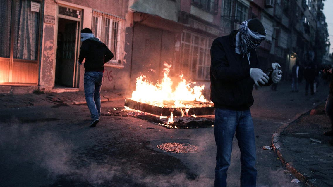 A masked man prepares to throw a petrol bomb toward police who used water cannon and teargas to disperse people protesting against security operations against Kurdish rebels in southeastern Turkey, in Istanbul, Sunday, Dec. 20, 2015. AP