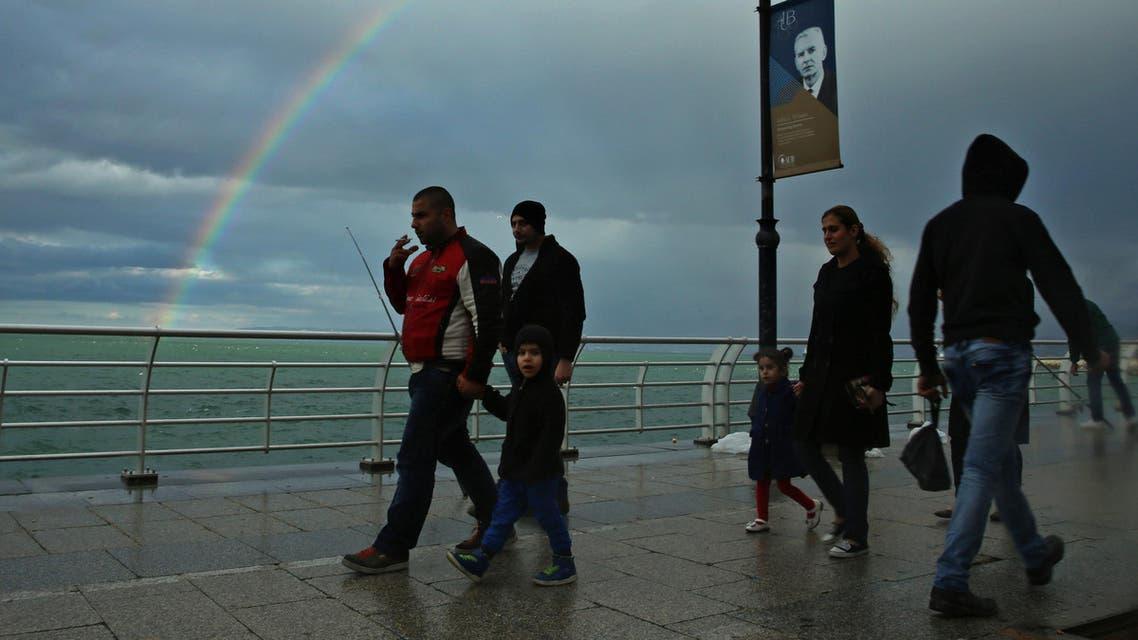 Lebanese walk along the Mediterranean Sea as a rainbow appears in a cloudy sky over Beirut, Lebanon, Sunday, Feb. 7, 2016. (AP)