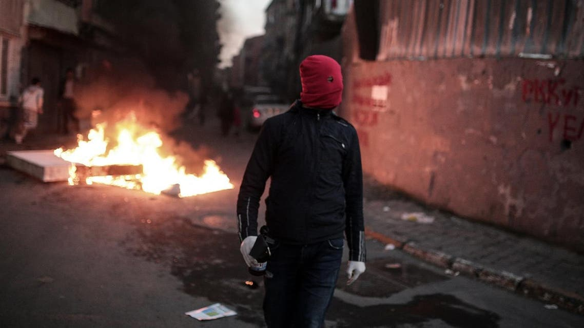 A masked man prepares to throw a petrol bomb toward police who use water cannons and teargas to disperse people protesting against security operations against Kurdish rebels in southeastern Turkey. (AP)