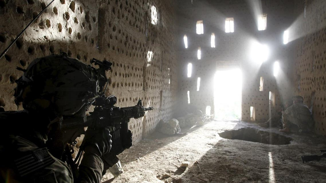 U.S. soldier Nicholas Dickhut from 5-20 infantry Regiment attached to 82nd Airborne points his rifle at a doorway after coming under fire by the Taliban while on patrol in Zharay district in Kandahar province, southern Afghanistan in this April 26, 2012 file photo. (Reuters)