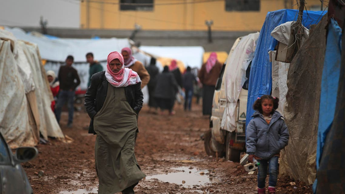 Syrian walk at a camp near the Bab al-Salam border crossing with Turkey, in Syria, Saturday, Feb. 6, 2016. Thousands of Syrians have rushed toward the Turkish border, fleeing fierce Syrian government offensives and intense Russian airstrikes. Turkey has promised humanitarian help for the displaced civilians, including food and shelter, but it did not say whether it would let them cross into the country. (AP Photo/Bunyamin Aygun) TURKEY OUT