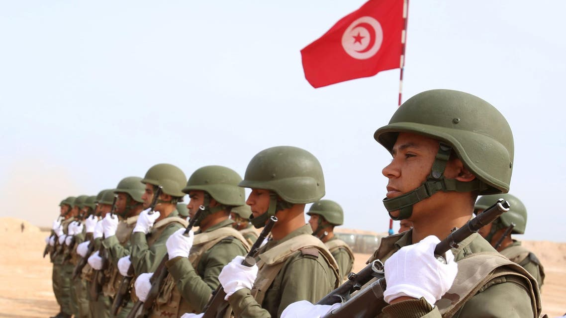 Tunisian soldiers listen to the national anthem along the frontier with Libya in Sabkeht Alyun,Tunisia February 6, 2016. REUTERS