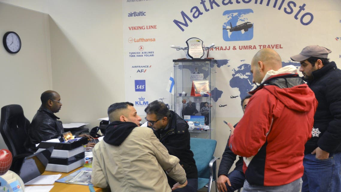 Travel agent Muhiadin Hassan (L) helps a group of migrants to arrange for flights to Baghdad at his office in Helsinki, Finland, February 10, 2016. Thousands of Iraqi refugees who arrived in Finland last year have decided to cancel their asylum applications and to return home voluntarily, citing family issues and disappointment with life in the frosty Nordic country. Picture taken February 10, 2016. REUTERS/Tuomas Forsell