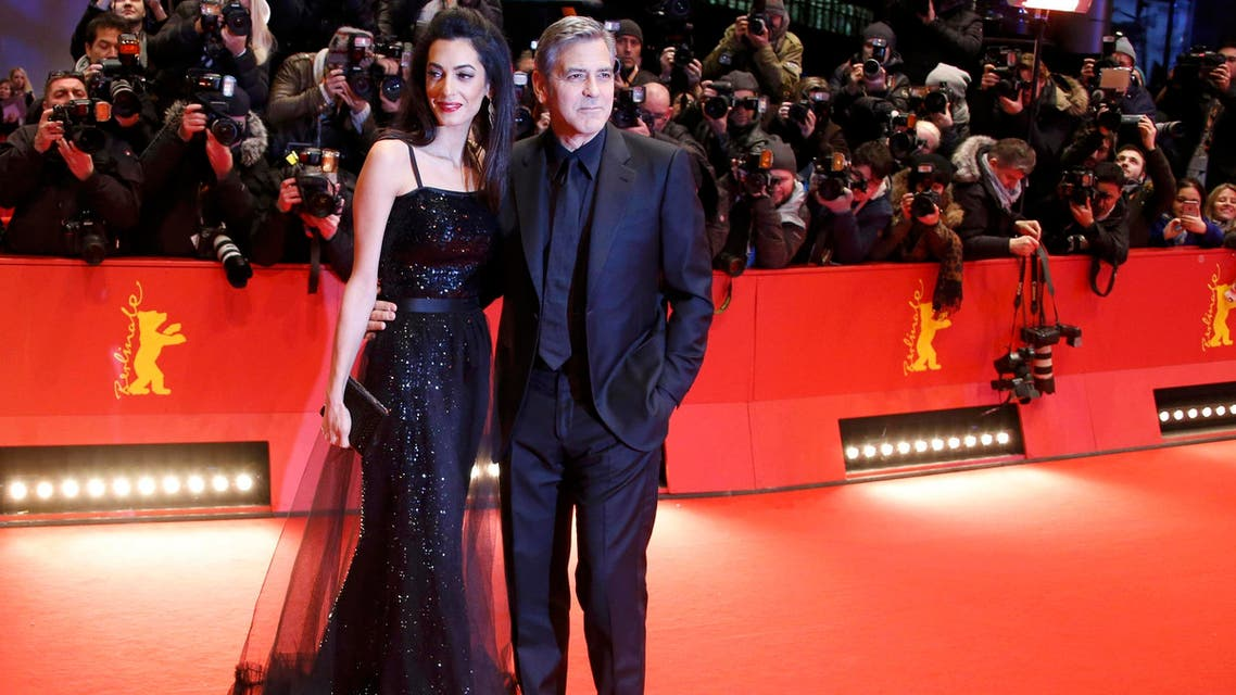 Cast member Clooney and his wife Amal arrive on red carpet for screening at opening gala of 66th Berlinale International Film Festival in Berlin. (Reuters)